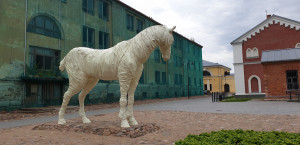 """Buvusių kareivinių fone į akis krenta milžiniško arklio skulptūra tarsi mumija – """"Tvirtovės vaiduoklis"""" (2017, skulpt. E. Perševic, dail. I. Kalita ir K. Čekotins)."""